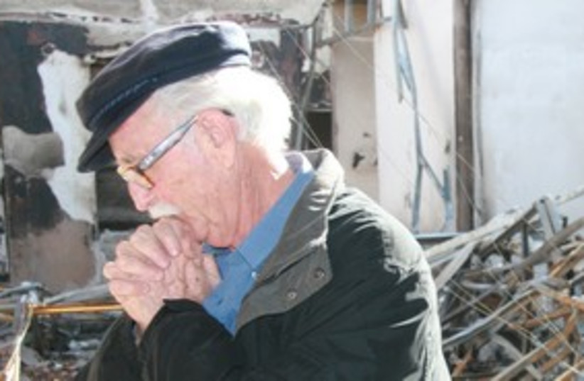 Man inspects damage of fire at Yemin Orde 311 (photo credit: DANIEL COHEN)