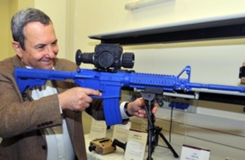 Barak shooting blue gun smiling 311 (photo credit: Ariel Harmoni/ Defense Ministry)