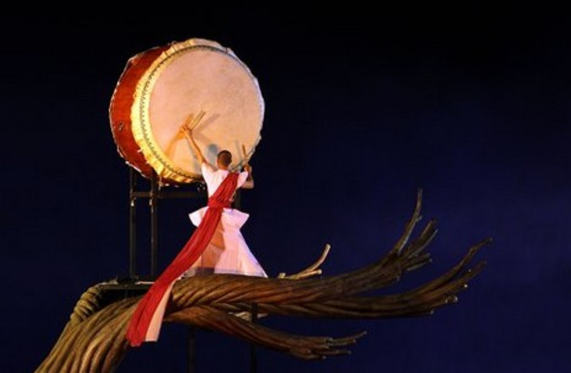 A Taiwanese performer plays a drum