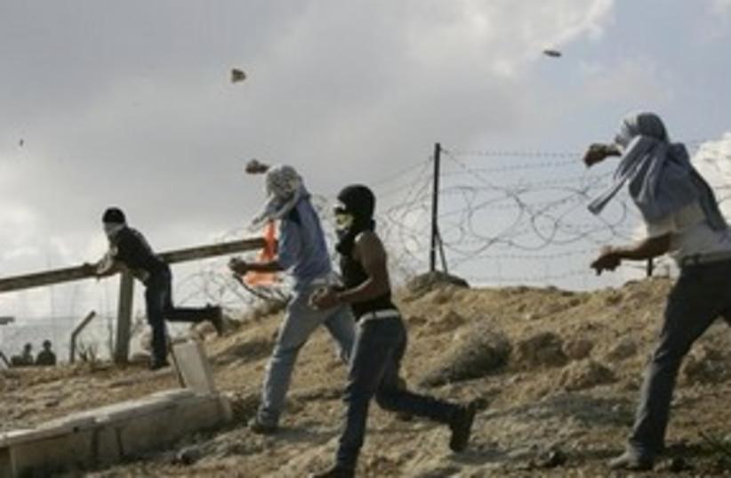 Bil'in demonstrators protestors slinging throwing rocks 311 (photo credit: AP)