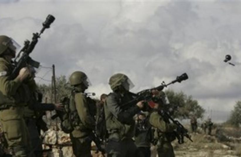 IDF soldiers firing stun grenades in Bil'in 311 (photo credit: AP)