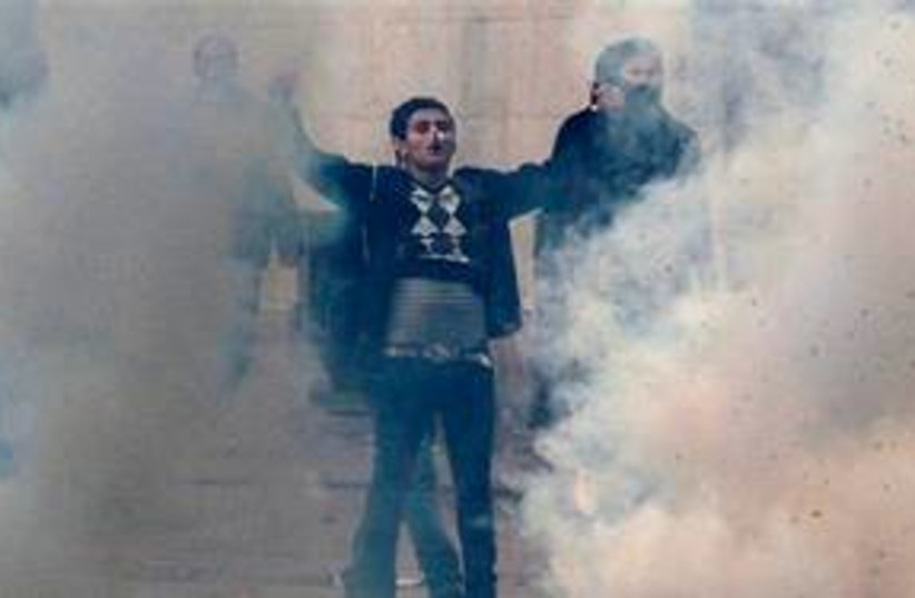Tunisian rioter stands in tear gas clouds 311 AP (photo credit: AP)