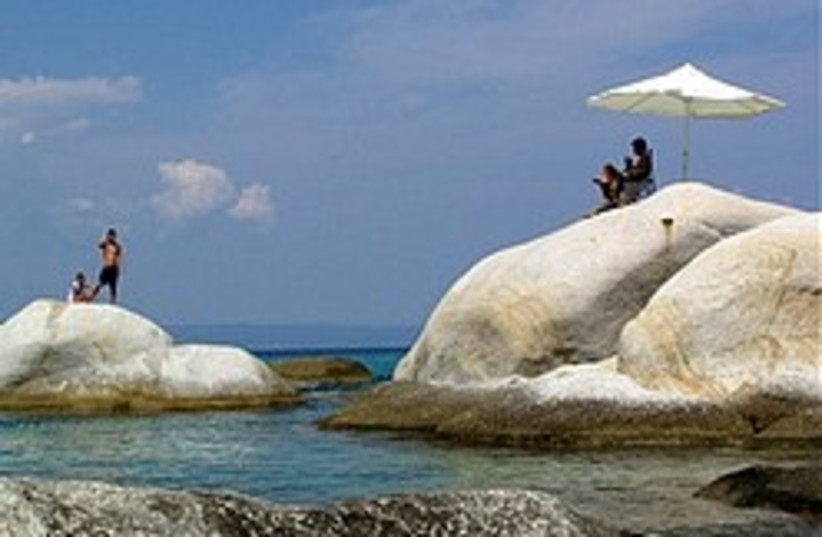 People sit on giant rocks as they enjoy the sea ne (photo credit: AP)