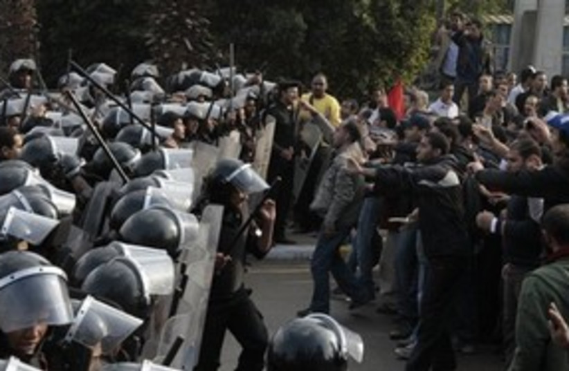 Protesters and riot police in Cairo (photo credit: Associated Press)