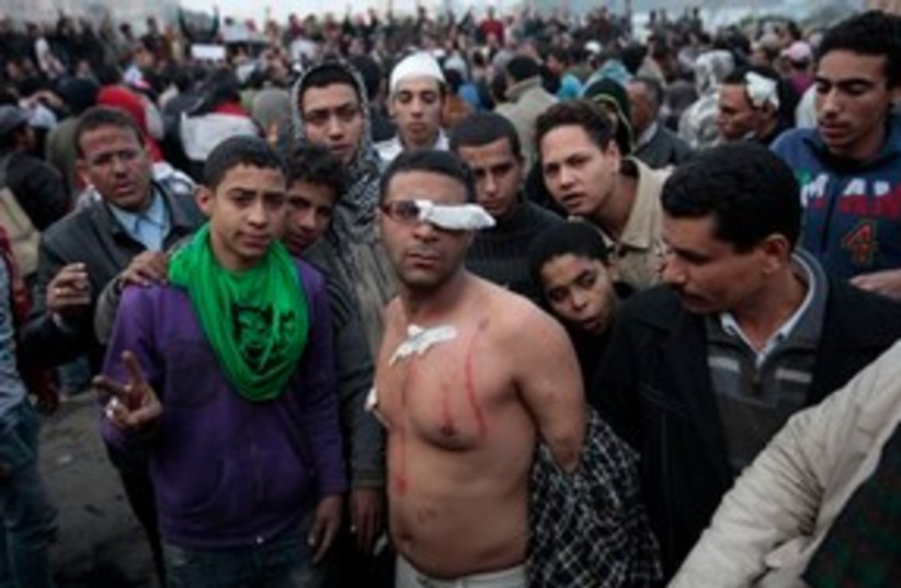 Egypt protests, topless man injured 311 (photo credit: AP Photo/Lefteris Pitarakis)