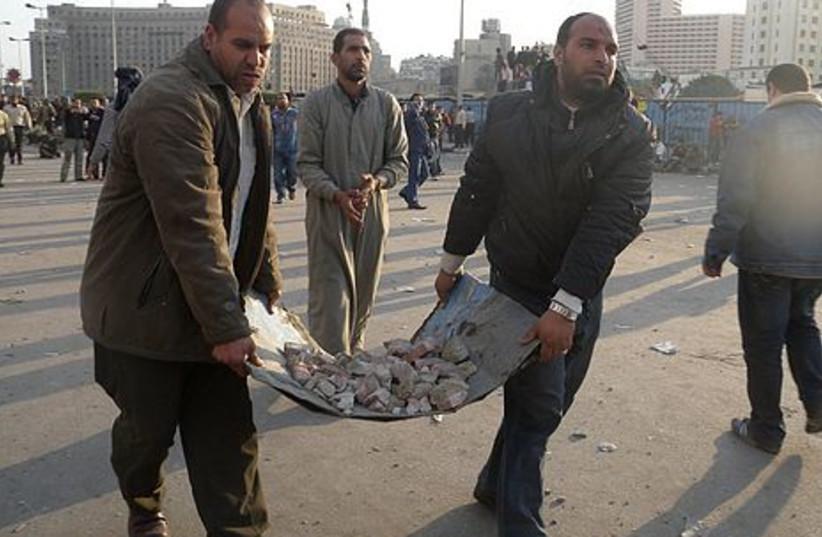 Egyptian men carrying rocks to throw