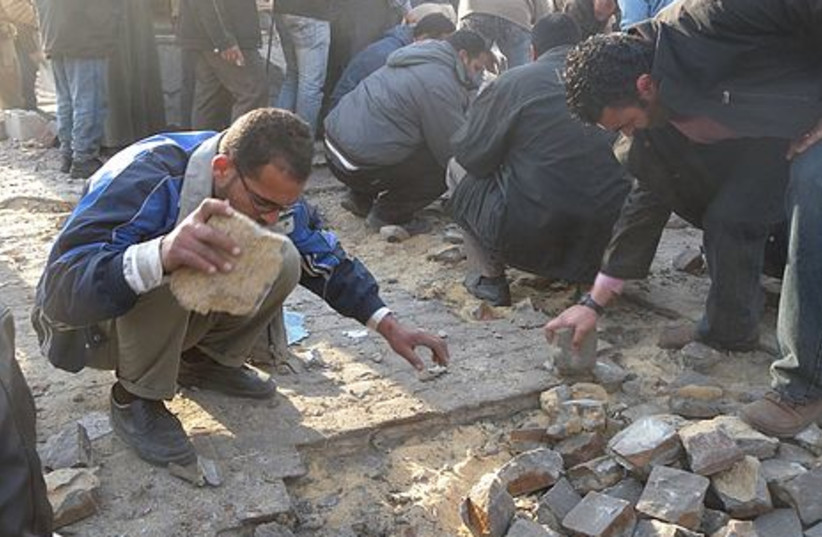 Egyptian men break up pavement so they have rocks