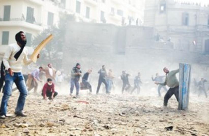 Throwing rocks stones Tahrir Square Cairo (photo credit: AP)