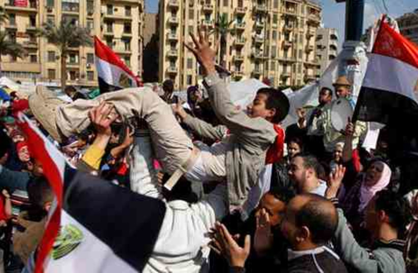 Egyptians dance and wave national flags