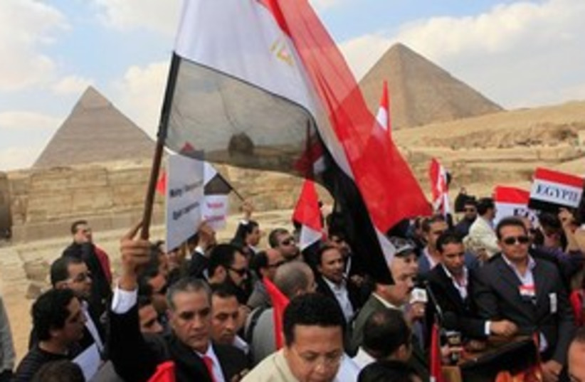 Egyptian protesters with flags at pyramids 311 (photo credit: AP Photo/Amr Nabil)