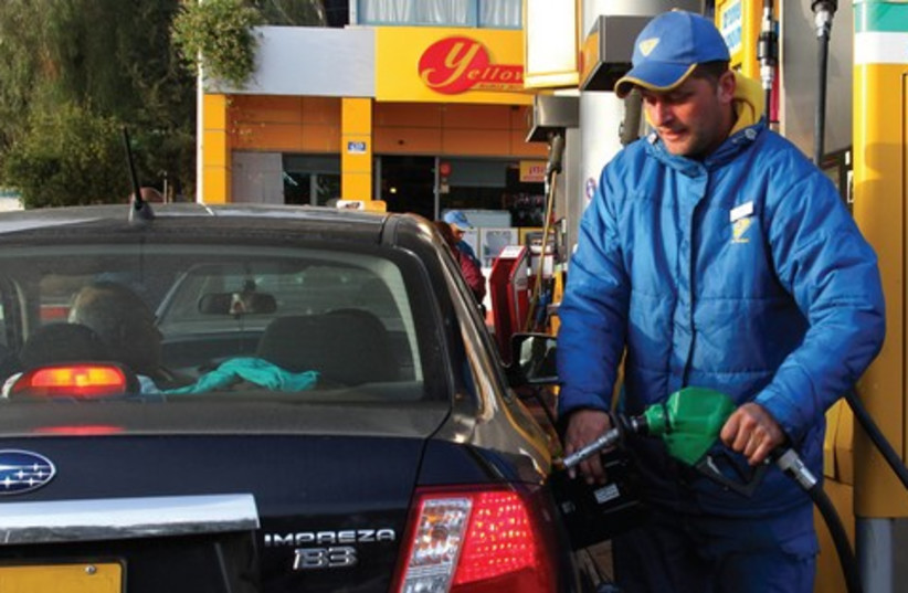 A man fills his tank at a gas station (photo credit: Marc Israel Sellem)