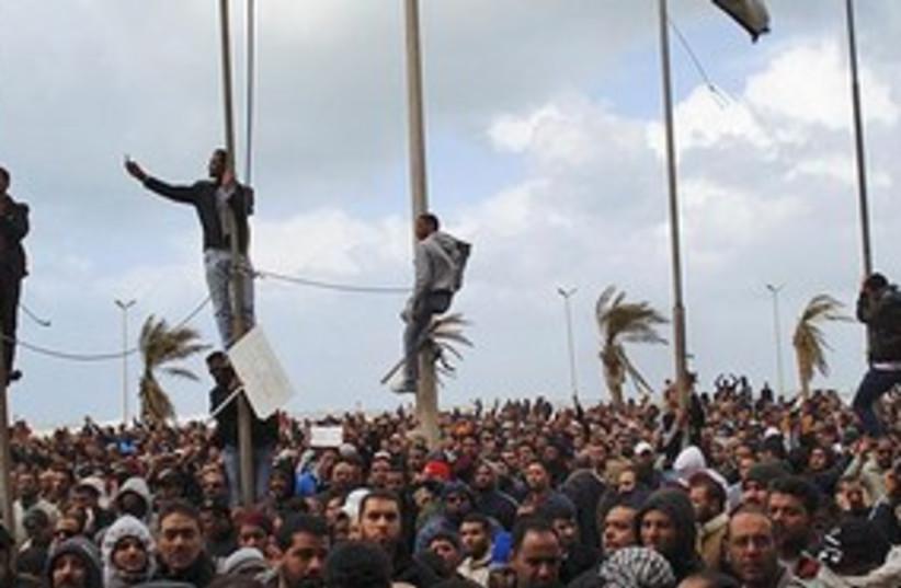 Libya protests men climbing 311 (photo credit: AP)