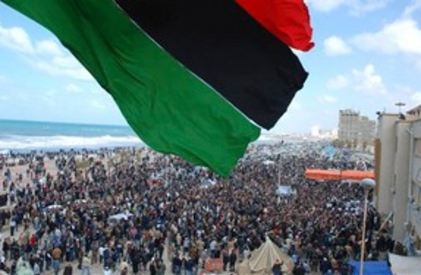 Libyan flag over protests (photo credit: AP)