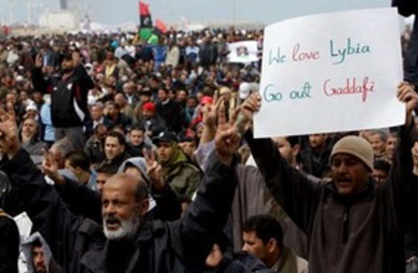 Libyan Protesters holding sign 311 (photo credit: AP Photo/Hussein Malla)
