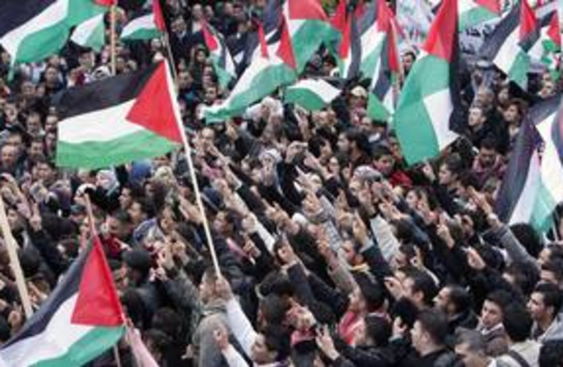 Palestinians wave flags during a protest  (R) 311 (photo credit: Reuters)