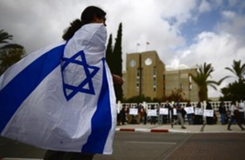 Protester wrapped in Israeli flag 311 R (photo credit: Reuters)