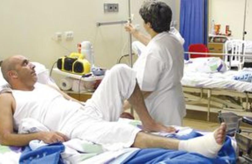 man in hospital bed with nurse 311 (photo credit: Ariel Jerozolimski)