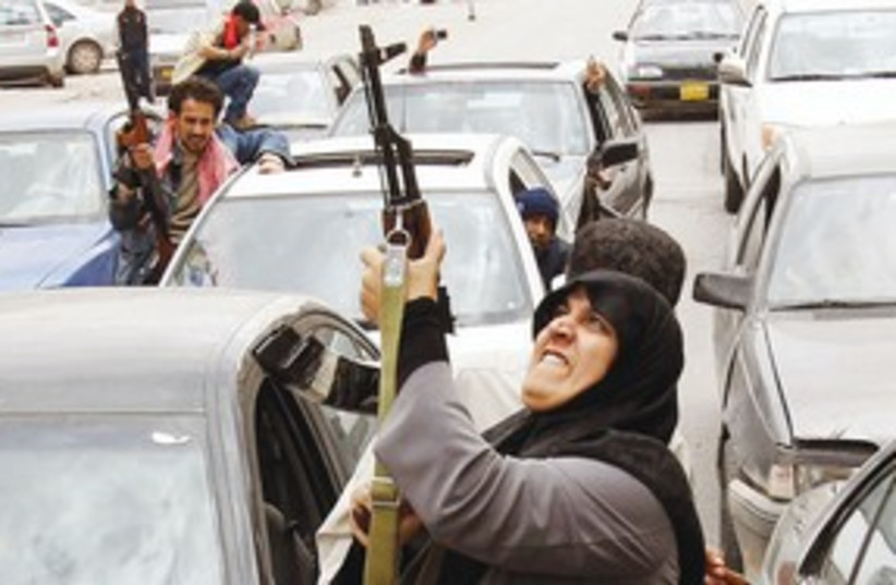 Rebel fighter shoots AK-47 in air 311 (photo credit: Reuters)