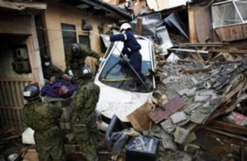 A body is pulled from rubble from Japan earthquake 311 (R) (photo credit: REUTERS/Damir Sagolj)