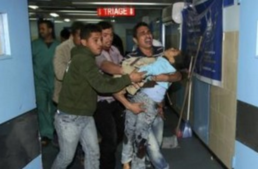 Palestinian boy carried into hospital Gaza injured 311 (R) (photo credit: REUTERS/Ismail Zaydah)