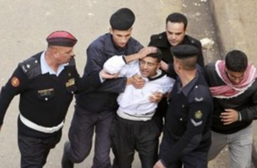 Injured protester escorted by Jordanian security 311 (R) (photo credit: REUTERS/Muhammad Hamed )