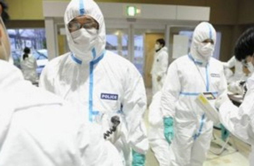 Japanese police after radiation screening 311 (R) (photo credit: REUTERS/Kyodo)