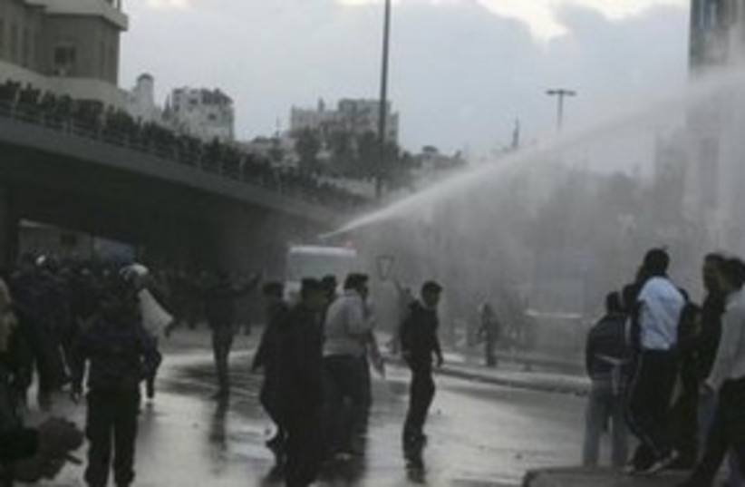 Jordanian protesters, police water canon 311 (R) (photo credit: REUTERS/Majed Jaber)