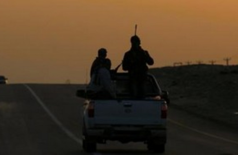 Rebel fighters drive towards Ras Lanuf, Libya 311 (R) (photo credit: REUTERS/Andrew Winning)