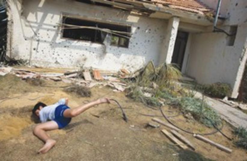 Boy looks for shrapnel_311 (photo credit: REUTERS)