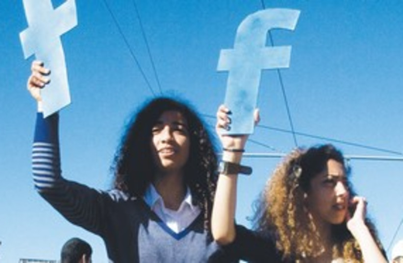 Moroccan women holding Facebook signs at protest 311 (R) (photo credit: Reuters)