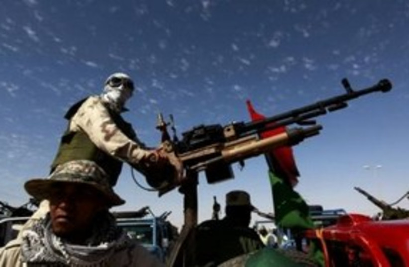 Libyan rebel with anti-aircraft gun 311 (R) (photo credit: REUTERS/Yannis Behrakis)