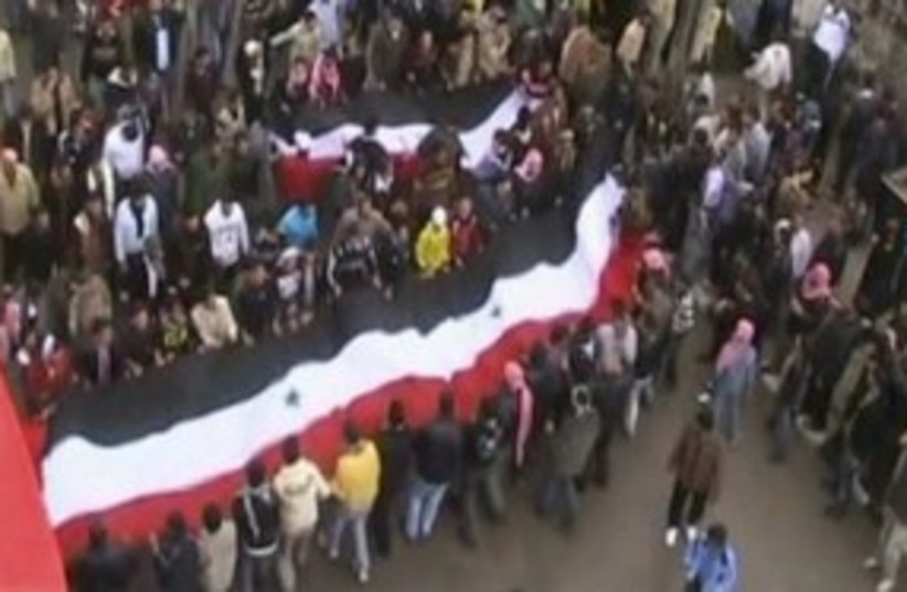 Syrian protesters in Deraa hoisting large flag 311 (R) (photo credit: REUTERS)