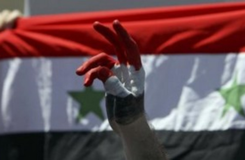 Syrian protester against flag 311 (R) (photo credit: REUTERS/Muhammad Hamed)