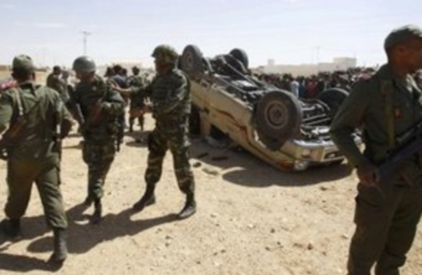Tunisian soldiers survey damage from Libyan troops 311 (R) (photo credit: REUTERS/Zoubei Souissi)