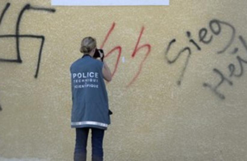 French police photograph neo-Nazi graffiti 311 (R) (photo credit: REUTERS)