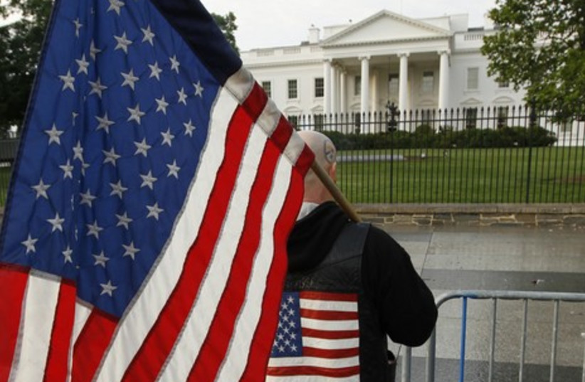Man with American flag outside White House