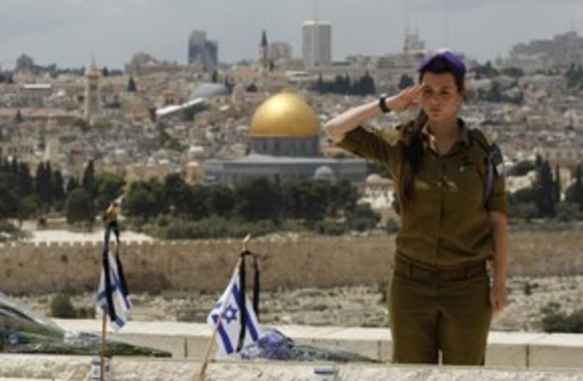 soldier salutes a soldier's grave_311 reuters (photo credit: BAZ RATNER / REUTERS)