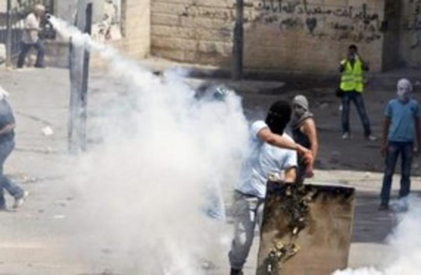 Palestinian throws back tear gas canister Silwan 311 (R) (photo credit: REUTERS/Nir Elias)