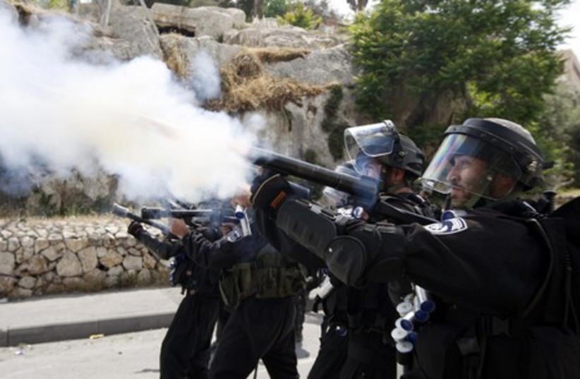 Police officers firing tear gas in Silwan clash