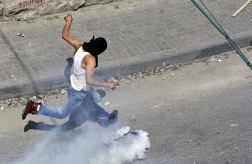 Palestinian kicking back a tear gas canister