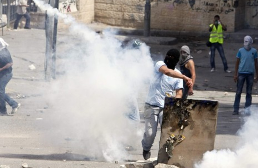 Palestinian throwing back a tear gas canister