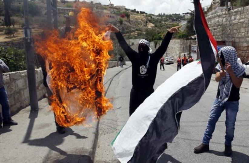 Palestinians burning a flag during Silwan clashes GALLERY (photo credit: REUTERS/Nir Elias)