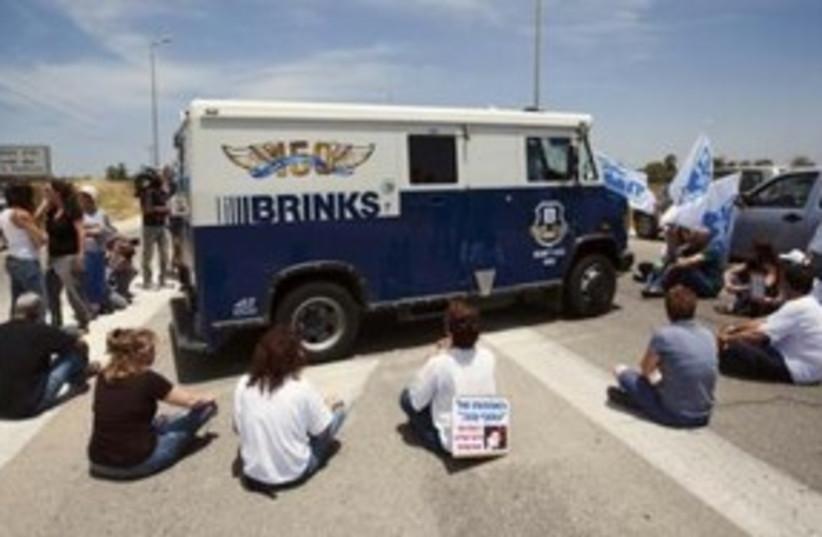 Schalit activists block 'Brinks' truck from reaching Gaza 31 (photo credit: REUTERS/Amir Cohen)