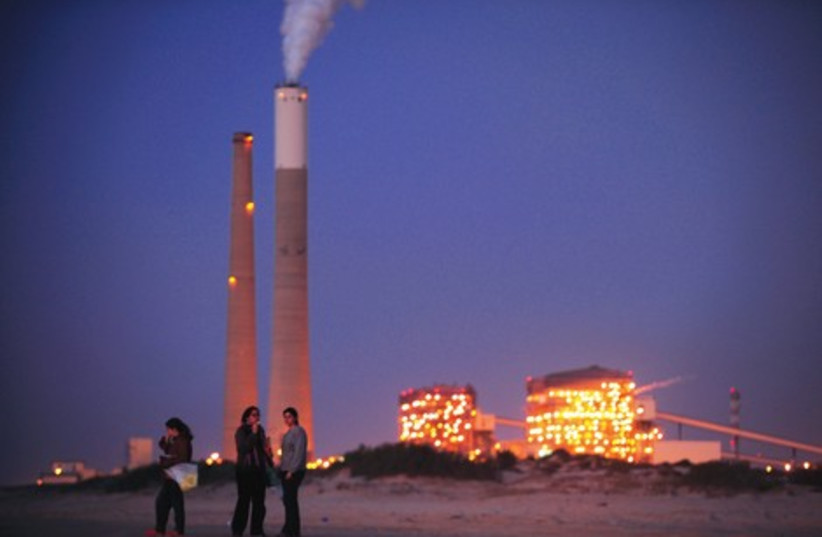 RUNNING LOW: Israelis stand on the beach in front of a coal  (photo credit: Amir Cohen)