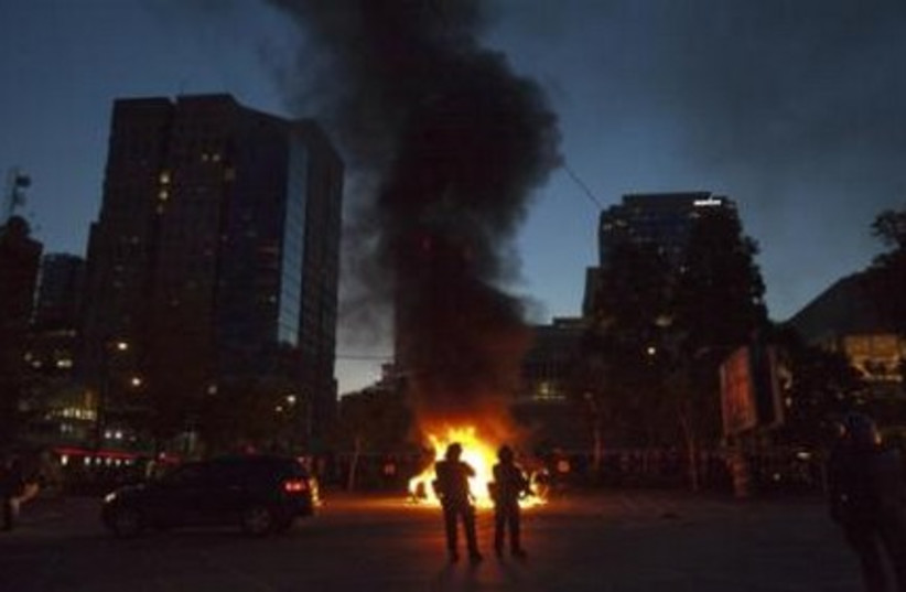 Police stand guard as police cars burn in Canada.