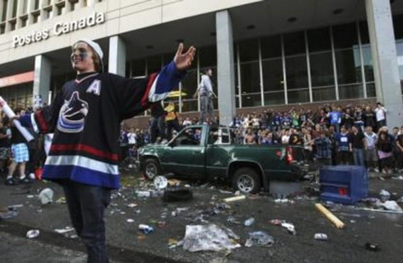 A Vancouver Canucks fan poses for photos.
