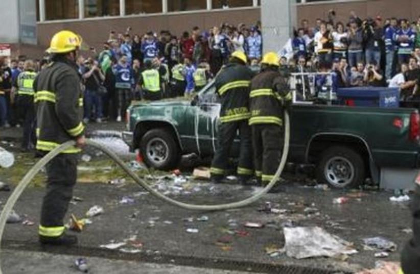 Canucks fans watch as firefighters douse a car.