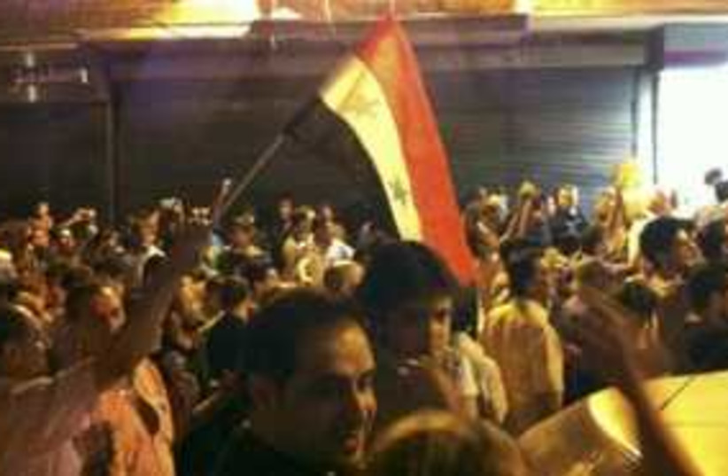 Syria protests at night with flag 311 (photo credit: REUTERS/Handout )