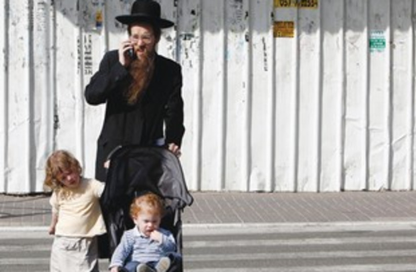 Haredi man with kids on mobile phone 311 (photo credit: REUTERS)