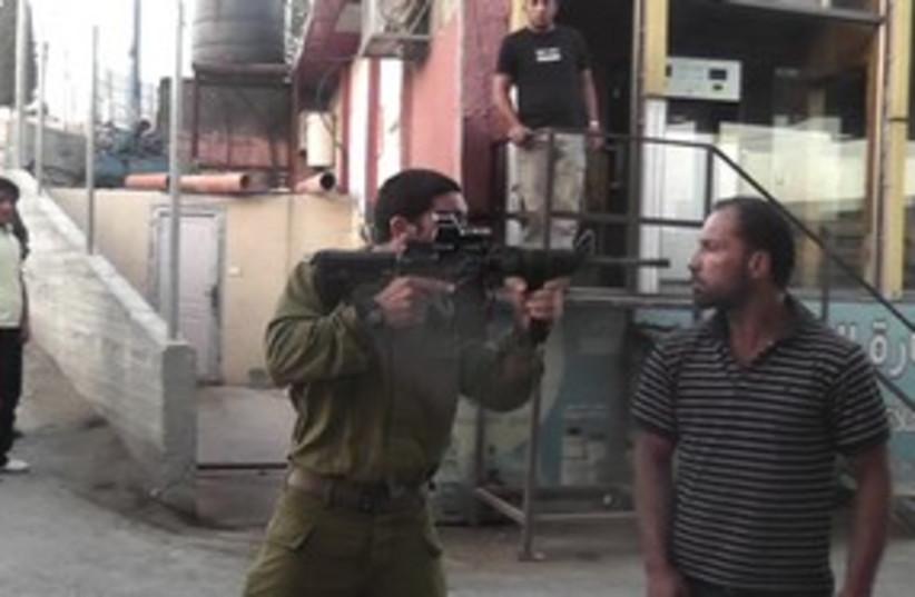 soldier points gun in palestinian's face_311 (photo credit: B'Tselem)